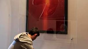 """Un employé de la Collection Lambert ramasse le verre brisé du """"Piss Christ"""", oeuvre du photographe américain Andres Serrano, vandalisée dimanche à Avignon. La Collection Lambert prévoit de rouvrir le musée d'Avignon aux visiteurs mardi, et dit avoir reçu"""