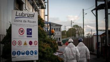 Deux travailleurs marchent vers l'usine Lubrizol près de Rouen, le lendemain de l'incendie
