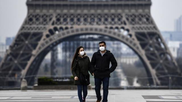 Deux personnes masquées devant la Tour Eiffel à Paris