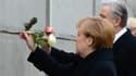 Angela Merkel et Klaus Wowereit, maire de Berlin, déposent une rose dans un morceau du Mur.