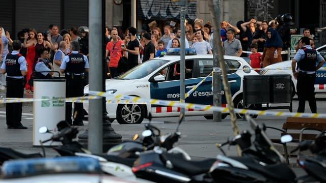 Des passants évacuant les lieux de l'attaque de Barcelone sous l'oeil de la police, le 17 août 2017.