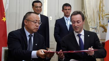Les président d'Airbus et CAS (au premier plan) paraphent le contrat, sous les regards de Manuel Valls et Li Keqiang (au second plan)