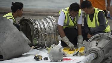 Des experts examinant les restes du moteur du Boeing de la compagnie Lion Air.
