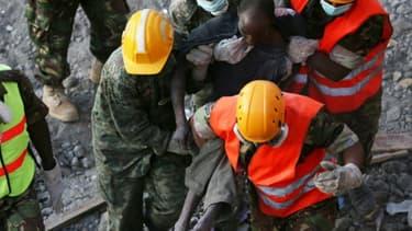 Des équipes de secours transportent un blessé après l'effondrement d'un immeuble à Nairobi, le 5 mai 2016 au Kenya
