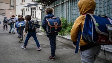 Photo d'élèves entrant en classe en respectant des mesures de distanciation, le 12 mai à Paris