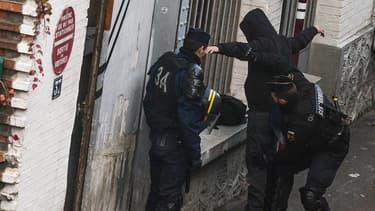 Des policiers fouillent un suspect à l'occasion d'une perquisition en Seine-Saint-Denis.
