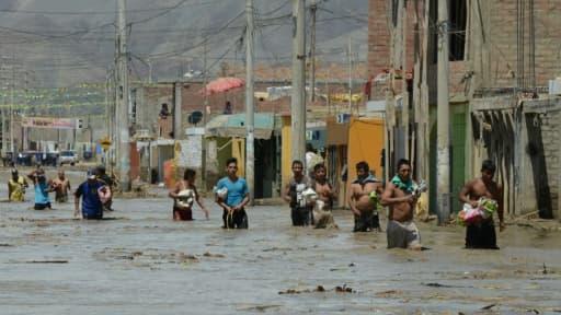 Des habitants de la commune de Huarmey, cité portuaire à 300 kilomètres au nord du Pérou est encerclée par la boue depuis les pluies diluviennes qui ont balayé le pays ces derniers jours, le 19 mars 2017