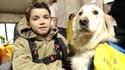 Le petit Adrien Derudder, jeune myopathe porte-parole de la 20e édition du Téléthon, pose en compagnie de son chien Willy, le 8 décembre 2006 à Paris.