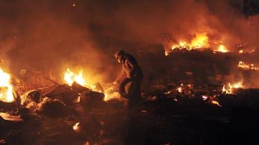 Un manifestant alimente les barricades enflammées en pneus, le 19 février, place de l'Indépendance, à Kiev.