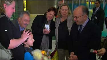Enzo dans les bras de sa maman à gauche, face au ministre du Budget, à droite, lors d'émouvantes retrouvailles.