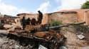 Soldats de la force de paix de l'Union africaine inspectant un de leurs chars détruit par les milices Chabaab à Mogadiscio. Les combats ont repris dimanche dans la capitale somalienne au lendemain de l'annonce par les rebelles qu'ils abandonnaient la vill