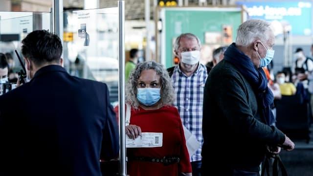 Des passagers, le visage couvert d'un masque pour se protéger du coronavirus, font la queue pour embarquer à l'aéroport de Bruxelles-Zaventem lors de sa réouverture, le 15 juin 2020