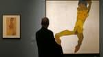 """Un homme en train de regarder l'oeuvre """"Homme assis"""" d'Egon Schiele au musée Leopold de Vienne en octobre 2012."""
