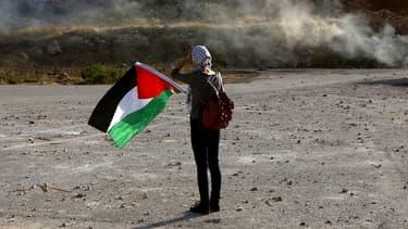Une manifestante brandit un drapeau palestinien en signe de solidarité à Ofer, en Cisjordanie. L'Assemblée nationale se prononcera, le 2 décembre, sur une proposition de résolution socialiste sur la reconnaissance d'un Etat de Palestine.
