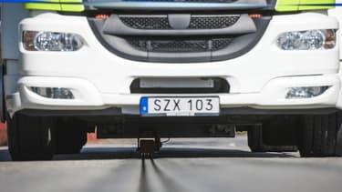 L'énergie électrique est transférée grâce à un bras amovible situé sous le véhicule qui entre en contact avec le rail situé au milieu de la route.