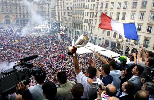 Sonny Anderson (trophée en main) et ses coéquipiers célèbrent la victoire en Coupe de la Ligue 2001 avec les supporters lyonnais depuis le balcon de l'Hôtel de Ville