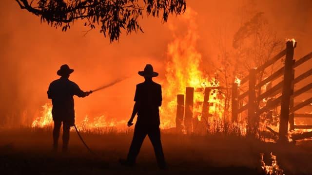 Des résidents défendent leur propriété d'un feu de brousse à Hillsville près de Taree, à 350km du nord de Sydney, le 12 novembre 2019