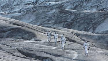 """Les astronautes d'""""Interstellar"""", explorant des contrées extra-terrestres."""