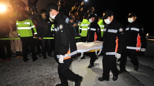 Des sauveteurs transportent un corps retrouvé dans le ferry, samedi.