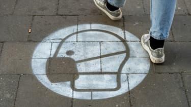 Un marquage au sol sur un trottoire appelle au port du masque à Berlin le 10 mars 2021
