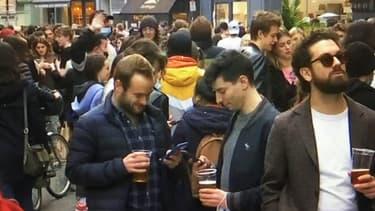 Des Parisiens en train de boire sur la chaussée à Paris.