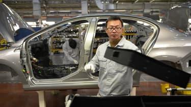 Un ouvrier sur une ligne d'assemblage de l'usine PSA de Wuhan, en Chine, en décembre 2013.