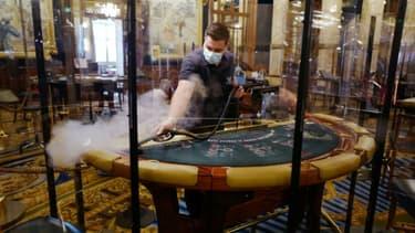 Un employé de casino désinfecte une table de blackjack avant la réouverture du casino de Monte-Carlo le 4 juin 2020 à Monaco