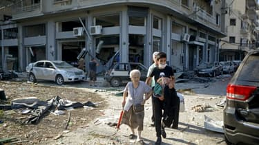 """Une femme est évacuée du quartier de Mar Mikhaël, le 5 août 2020, le """"coeur battant"""" de Beyrouth dévasté par les explosions de la veille"""