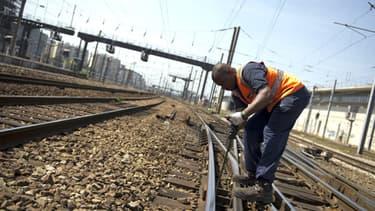 Un agent de la SNCF entretient le réseau à Paris le 14 juillet 2013.
