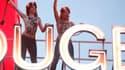 """Deux Femen ont bravé la pluie pour dénoncer """"'l'industrie du sexe"""", lundi 6 octobre, sur le toit du Moulin Rouge. Un action qui coïncidait avec les 125 ans du temple parisien du French Cancan."""