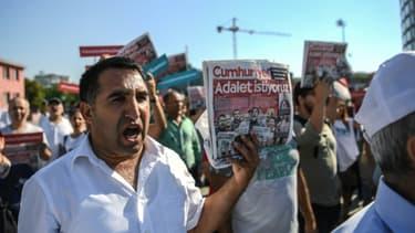 """Un manifestant brandit un exemplaire du quotidien Cumhuriyet avec le gros titre """"Nous voulons la justice"""" en une, le 24 juillet à Istanbul"""