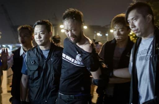 Ken Tsang (c), militant du Parti civique, est emmené par des policiers lors des manifestations pour la démocratie, le 15 octobre 2014 à Hong Kong