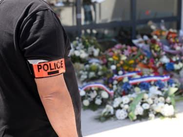 Un policier se recueille devant les fleurs déposées en hommage à Éric Masson, dimanche 9 mai 2021, devant son commissariat d'Avignon