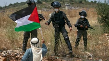 Un Palestinien fait face à des forces de sécurité israéliennes pendant une manifestation contre le projet d'annexion israélien, près de Tulkarem, dans le nord de la Cisjordanie occupée, le 5 juin 2020