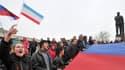 A Simferopol, en Crimée, des activistes pro-russes brandissent samedi un drapeau russe géant près d'une statue de Lénine