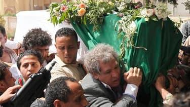 Quelque 2.000 personnes brandissant des drapeaux et des portraits de Mouammar Kadhafi ont assisté à Tripoli aux funérailles de son fils cadet Saïf al Arab, tué samedi soir lors d'un raid de l'Otan. /Photo prise le 2 mai 2011/REUTERS/Louafi Larbi