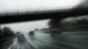 Conduite par temps de pluie sur une autoute. (illustration)