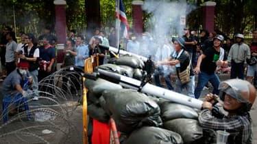 """Barricade de fortune érigée par des """"chemises rouges"""" dans le centre de Bangkok, où la situation est explosive après une nuit d'affrontements entre soldats et manifestants antigouvernementaux qui ont fait un mort et neuf blessés, dont un chef militaire de"""