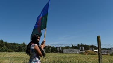 Sur cette photo du 24 juin 2017, une protestataire brandit un drapeau rom devant la porcherie de Lety, construite dans les années 1970 sur le site d'un ancien camp nazi