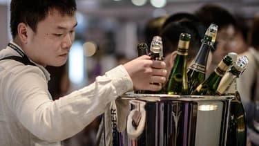 Un Chinois au salon du vin de Hong Kong, en mai 2014, regardant des bouteilles de Champagne.
