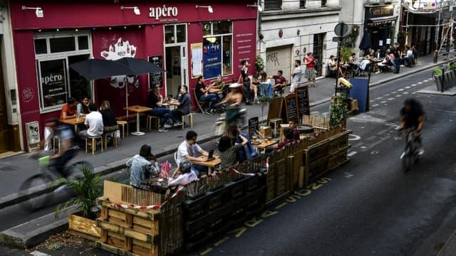 Des personnes prennent un verre à la terrasse élargie d'un bar à Paris, le 23 juillet 2020
