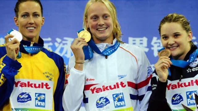 Mélanie Hénique (à droite) sur le podium du 50m papillon