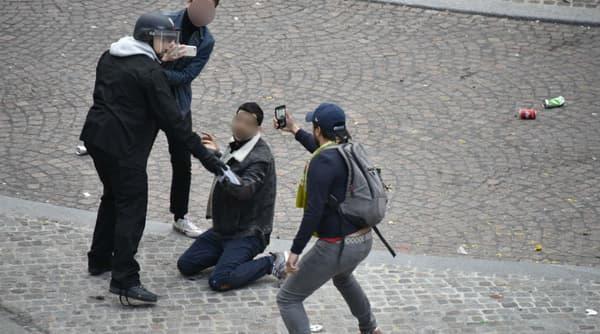 Alexandre Benalla maintient à terre le jeune manifestant place de la Contrescarpe à Paris, tandis qu'un homme filme la scène le 1er mai dernier.