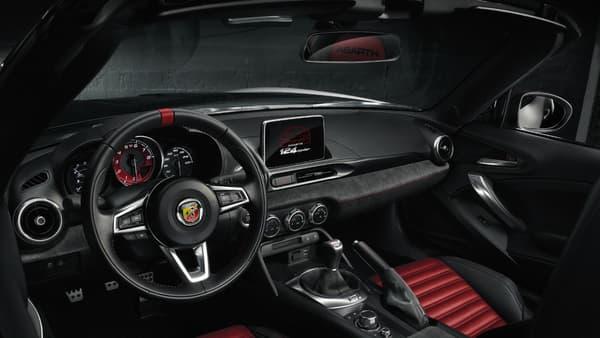 L'habitacle de l'Abarth 124 Spider ajoute à la livrée noire et blanche de la carrosserie une sellerie rouge qui renforce son look sport.