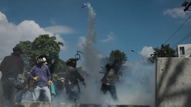 Les manifestants anti-gouvernement renvoient du gaz lacrymogène aux forces de l'ordre à Bangkok en Thaïlande le 1er décembre 2013.