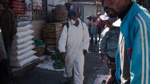 Un homme désinfecte les rues du marché d'Antananarivo, le 10 octobre 2017.