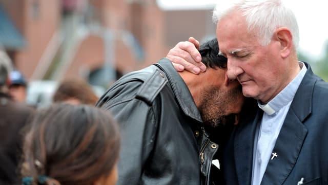 Le père Arthur, en 2012, conforte un homme expulsé de son camp par les forces de police