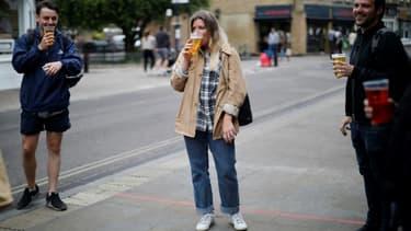 Des clients d'un pub à Londres boivent leur bière dans des verres en plastique à l'extérieur de l'établissement, en raison des restrictions contre le coronavirus alors en vigueur, le 5 juin 2020