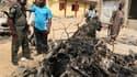 Policiers autour de la voiture piégée utilisée dans l'attentat qui a visé dimanche l'église catholique Sainte-Theresa à Madala, près de la capitale nigériane Abuja. L'attaque a été revendiquée par la secte islamiste Boko Haram. /Photo prise le 25 décembre