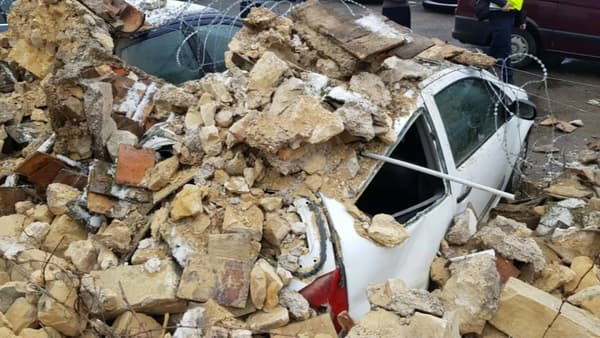 Un mur d'enceinte s'est effondré sur les véhicules des fonctionnaires de police.